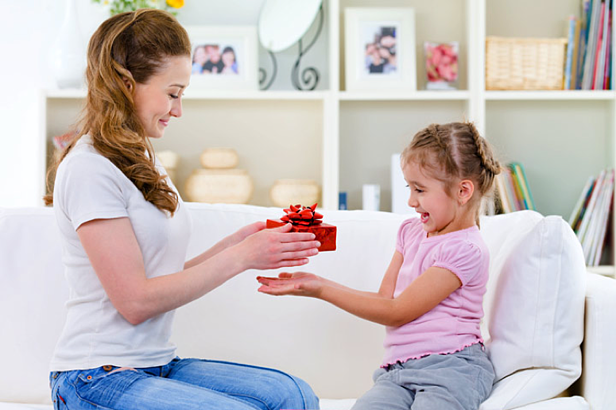 woman gifting a little girl with a gift box